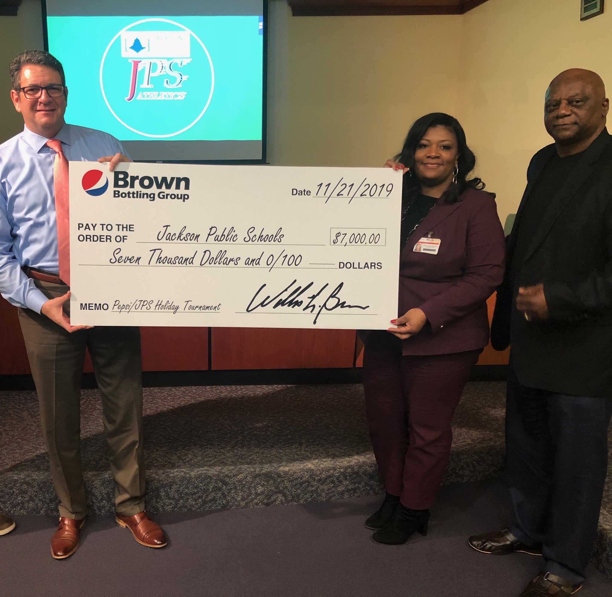 A Brown Bottling representative presents the 2019 sponsorship check for the Pepsi/JPS Holiday Tournament to representatives with Jackson Public Schools.